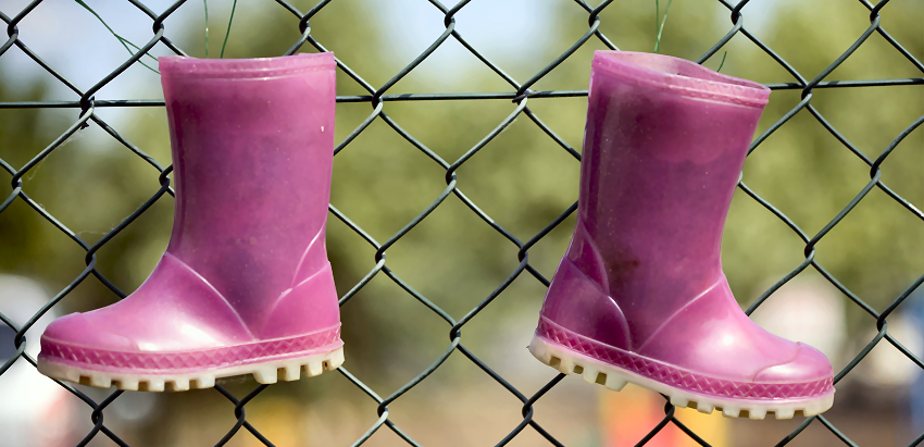 Purple boots on a fence